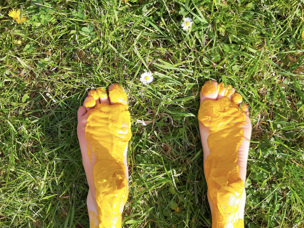 mustard - vibrant image of feet covered in mustard lying on grass